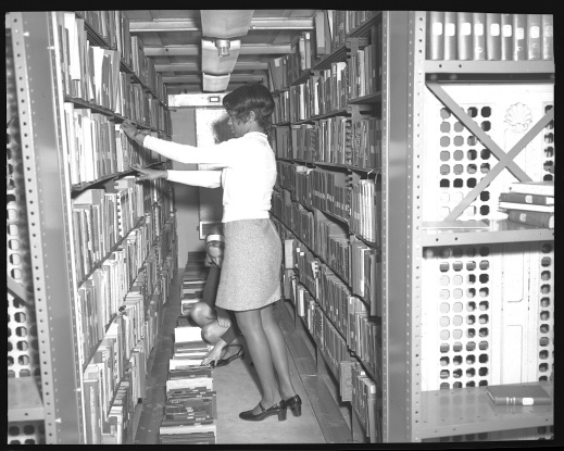 Crowded stacks, 1970. Photograph shows an African American employee of the Library of Congress among crowded book shelves with another employee. Photo courtesy Library of Congress Prints and Photographs Division Washington, D.C. https://www.loc.gov/item/2017646178/