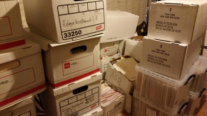 Storage room at the Refugee Resettlement Office with boxes and cabinets containing stacke from floor to ceiling. Photo courtesy the Archives of The Episcopal Diocese of Olympia.